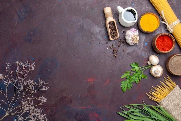 Widok z góry różne przyprawy z zieleniną i surowym makaronem na ciemnej powierzchni pikantnej ostrej papryki