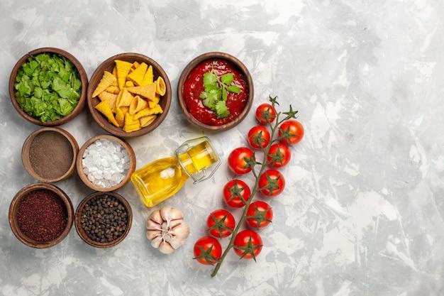 Widok z góry różne przyprawy z zielonymi pomidorami i olejem na białym biurku
