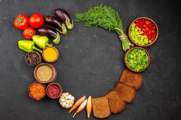 Widok z góry różne przyprawy z zielonymi warzywami i ciemnymi bochenkami chleba na ciemnym biurku przyprawy do sałatek chleb zdrowa żywność