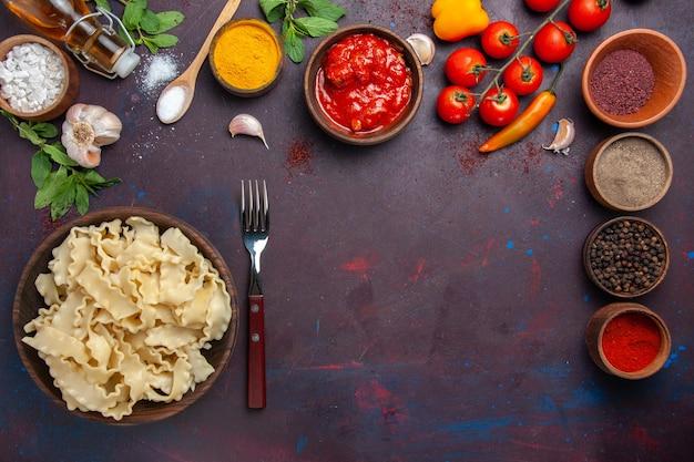 Widok z góry różne przyprawy ze świeżymi pomidorami i ciastem w ciemnej przestrzeni