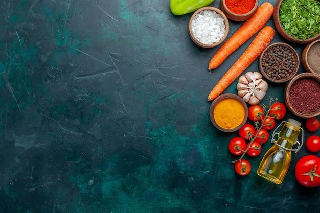 Widok z góry różne przyprawy ze świeżymi pomidorami na ciemnozielonym tle składnik produkt posiłek żywność warzywo