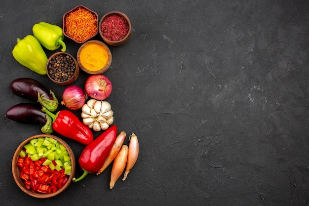Widok z góry różne przyprawy ze świeżymi warzywami na ciemnym tle dojrzały posiłek sałatka warzywna