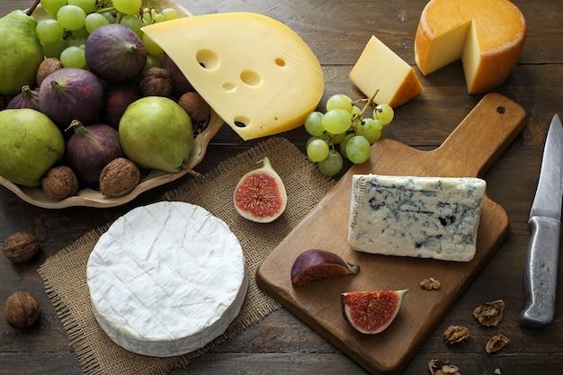 Widok z góry różne rodzaje serów i owoców na rustykalnym drewnianym stole