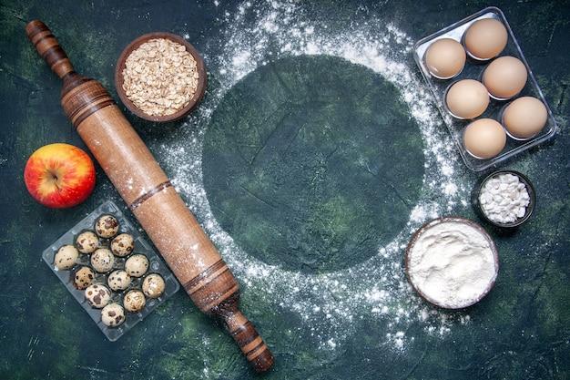 Widok z góry różne składniki ciasta zboża z białej mąki i jajka na ciemnoniebieskiej powierzchni