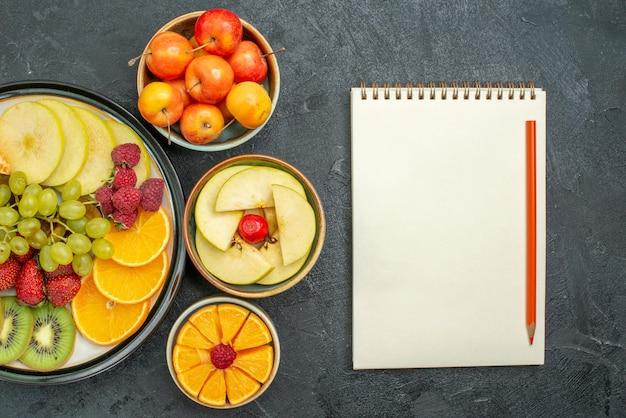 Widok z góry różne składy owoców świeże, łagodne i pokrojone owoce na ciemnej podłodze, świeże owoce łagodne zdrowie dojrzałe