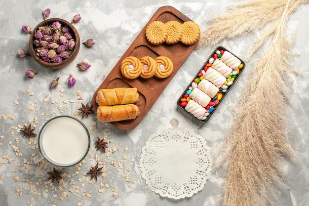 Widok z góry różne słodkie rzeczy cukierki i ciasteczka na białej powierzchni cukru biszkoptowe słodkie ciasto ciastko