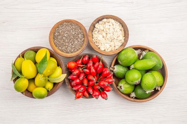 Widok z góry różne świeże owoce wewnątrz talerzy na białym tle egzotyczna dojrzała dieta zdrowe życie tropikalny kolor