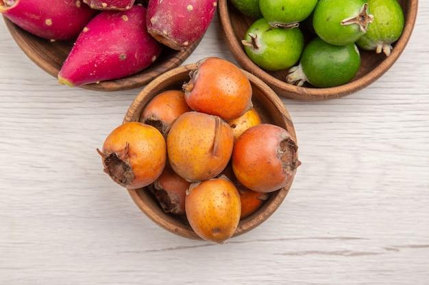 Widok z góry różne świeże owoce wewnątrz talerzy na białym tle egzotyczna tropikalna dojrzała dieta kolor zdrowe życie