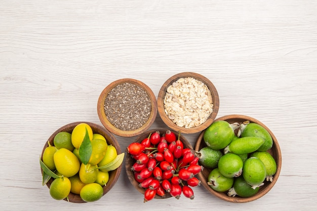Widok z góry różne świeże owoce wewnątrz talerzy na białym tle egzotyczne dojrzałe zdrowe życie tropikalny kolor
