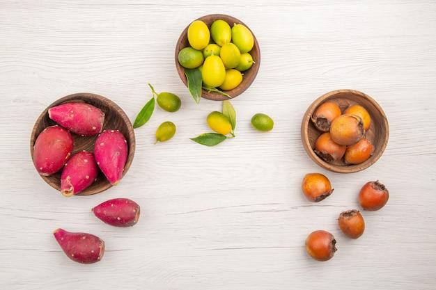 Widok z góry różne świeże owoce wewnątrz talerzy na białym tle owoce tropikalne dojrzałe diety egzotyczny kolor zdrowe życie