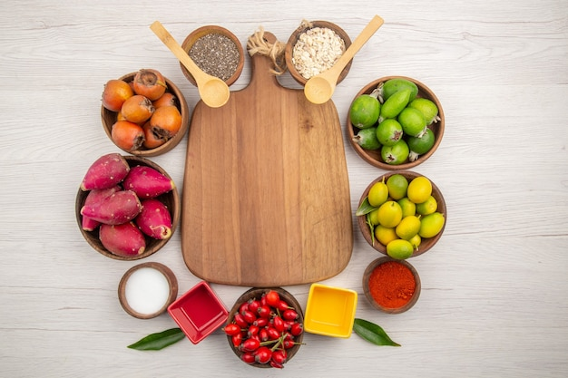 Widok z góry różne świeże owoce wewnątrz talerzy na białym tle tropikalna dojrzała zdrowa dieta kolorowa egzotyczna