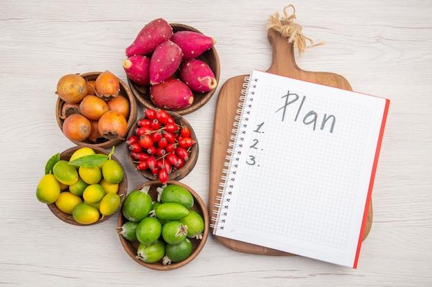 Widok z góry różne świeże owoce wewnątrz talerzy z notatnikiem na białym tle kolor tropikalne zdrowie egzotyczne drzewo jagodowe dojrzałe
