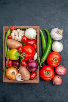Widok z góry różne świeże warzywa na ciemnym biurku sałatka warzywa świeże dojrzałe