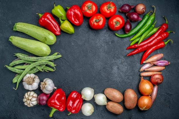 Widok z góry różne świeże warzywa na ciemnym stole dojrzała sałatka warzywna w świeżych kolorach