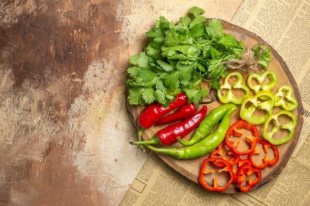 Widok z góry różne warzywa pokrojone na kawałki na okrągłej drewnianej desce na bursztynowym tle