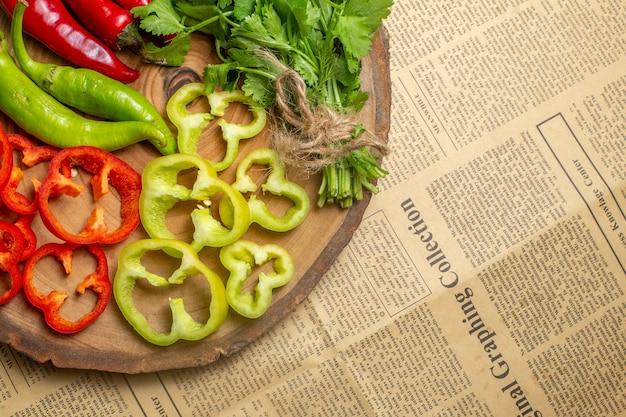 Widok z góry różne warzywa pokrojone na kawałki na okrągłej drewnianej desce na gazecie