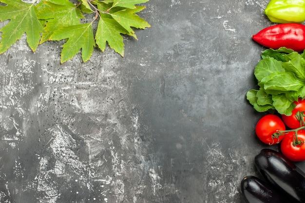 Widok z góry różne warzywa pomidory papryka bakłażany na szarym tle