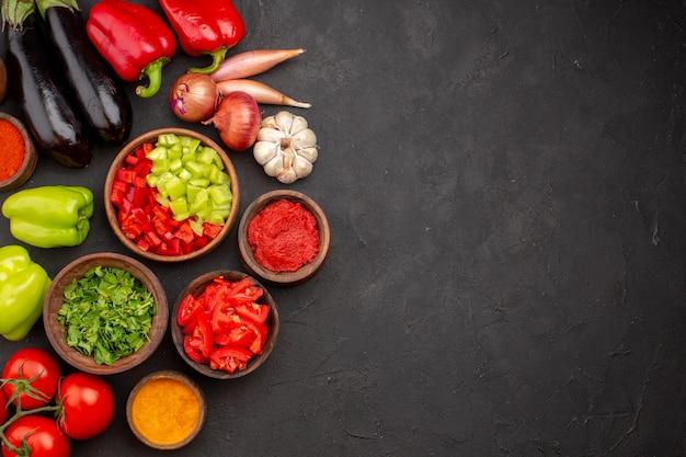 Widok z góry różne warzywa świeże i dojrzałe z przyprawami i zieleniną na szarym tle sałatka dojrzały posiłek zdrowotny
