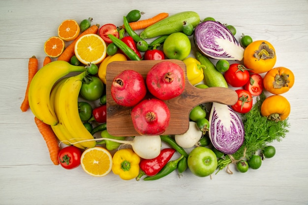 Widok z góry różne warzywa z owocami na białym tle żywność dieta zdrowie dojrzała kolorowa sałatka