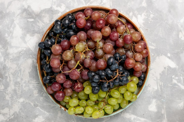 Widok z góry różne winogrona soczyste, łagodne, kwaśne owoce na jasnym białym biurku