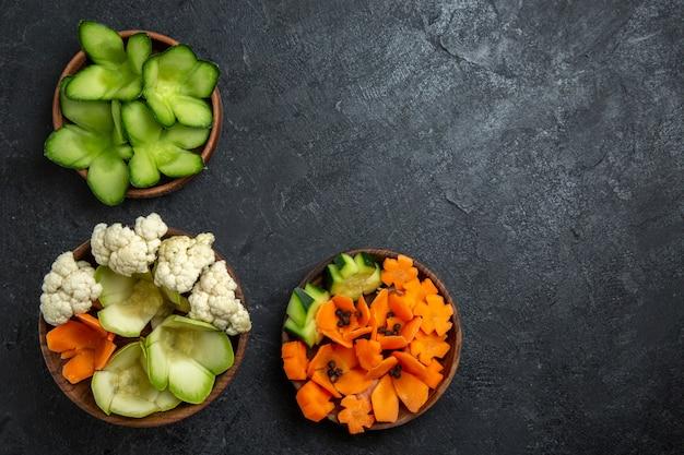 Widok z góry różne zaprojektowane warzywa w doniczkach na ciemnoszarej przestrzeni