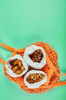 Widok z góry różnego rodzaju orzechów na stole w papierowej torbie w torbie na zakupy na zielonej powierzchni