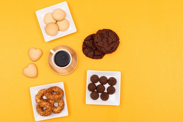 Widok z góry różnych ciasteczek w kwadratowe talerze i filiżankę kawy na żółtej powierzchni