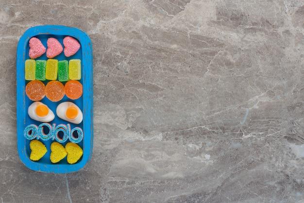 Widok z góry różnych cukierków na niebieskim drewnianym talerzu na szarym tle.