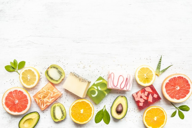 Widok z góry różnych kolorowych ręcznie robionych mydeł organicznych ułożonych z owoców cytrusowych, ziół, nasion chia i aloesu.