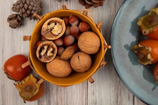 Widok z góry różnych orzechów, takich jak orzechy włoskie i orzechy laskowe, na wiadrze z miękkimi świeżymi persimmons na talerzu na szarej drewnianej ścianie
