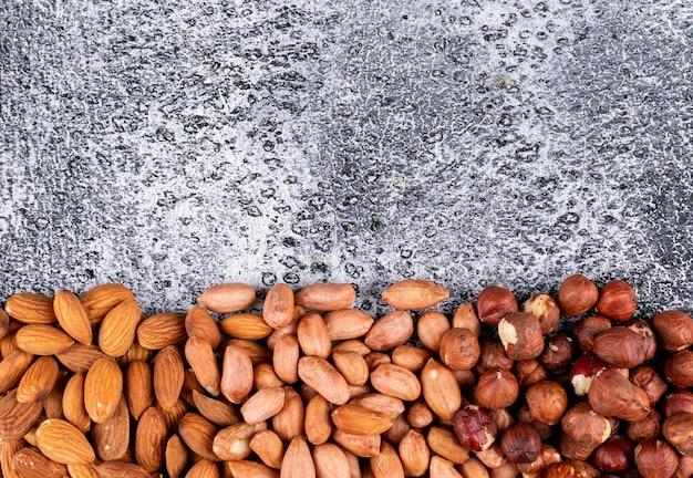 Widok z góry różnych orzechów z orzechami pekan, pistacjami, migdałami, orzeszkami ziemnymi, orzechami nerkowca, orzeszkami piniowymi na stole z ciemnego kamienia