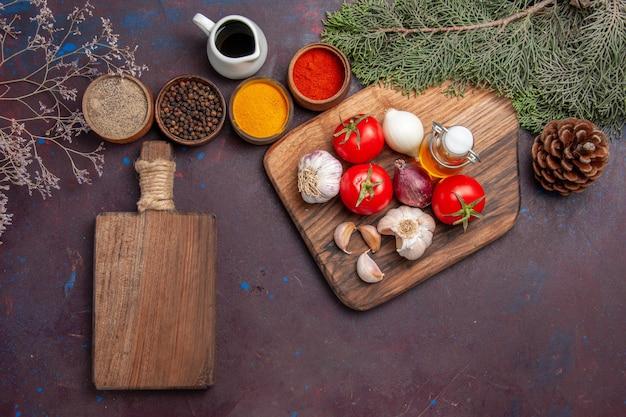 Widok z góry różnych przypraw ze świeżymi warzywami na czarnym stole
