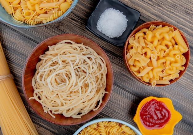 Widok z góry różnych rodzajów makaronów jak makaron spaghetti rotini i inne z solą i keczupem na drewnianej powierzchni