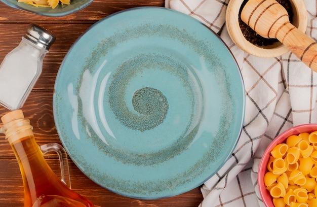 Widok z góry różnych rodzajów makaronów w miseczkach sól czarny pieprz masło wokół płyty na powierzchni drewnianych