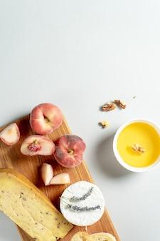 Widok z góry różnych rodzajów serów na drewnianej desce do krojenia. ser z brzoskwinią figową, miodem, ciabattą i orzechami, kieliszek czerwonego wina. stylowe jedzenie mieszkanie leżało na szarym tle. skopiuj miejsce nieostrość