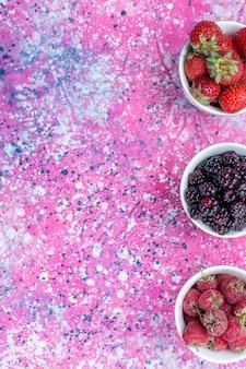 Widok z góry różnych świeżych jagód wewnątrz białych filiżanek na lekkim, świeżo kwaśnym owocu jagodowym