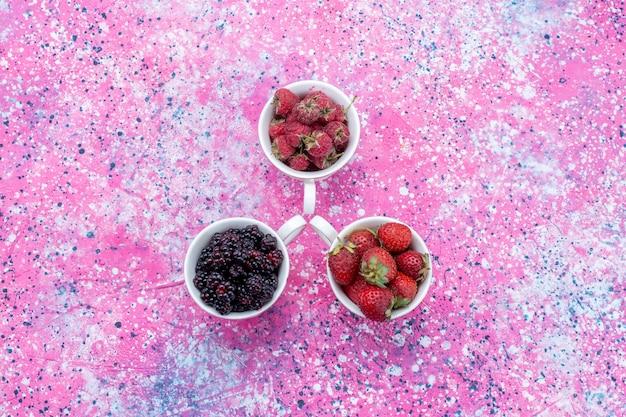 Widok z góry różnych świeżych jagód wewnątrz kubków na jasnofioletowych, świeżych owocach jagodowych
