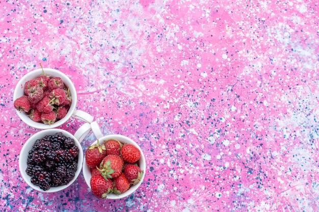 Widok z góry różnych świeżych jagód wewnątrz kubków na jasnym fioletowym biurku, świeże owoce jagodowe