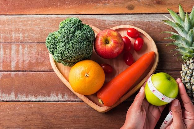 Widok z góry różnych świeżych organicznych owoców i warzyw w talerz serca i ręce kobiety