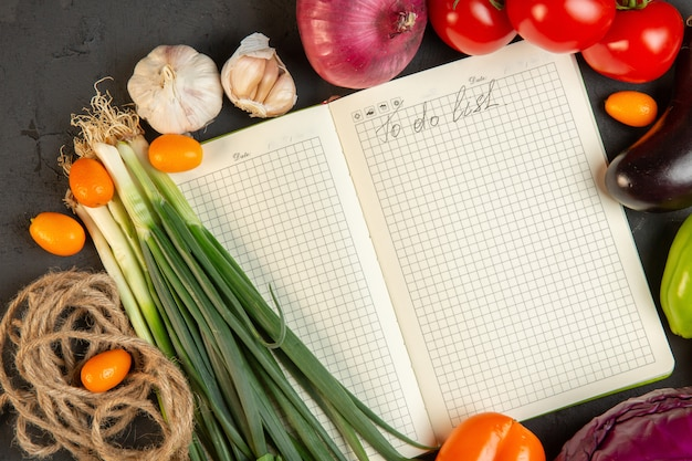 Widok z góry różnych świeżych warzyw pomidory zielona cebula i czosnek z notebookiem w środku na ciemno