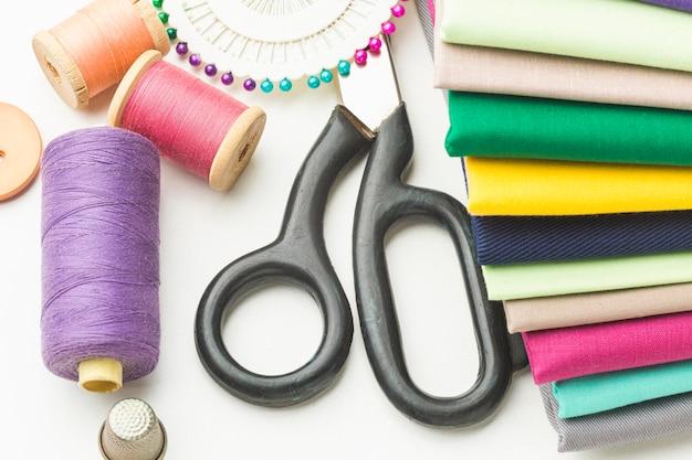 Widok z góry różnych tkanin z nitką i nożyczkami