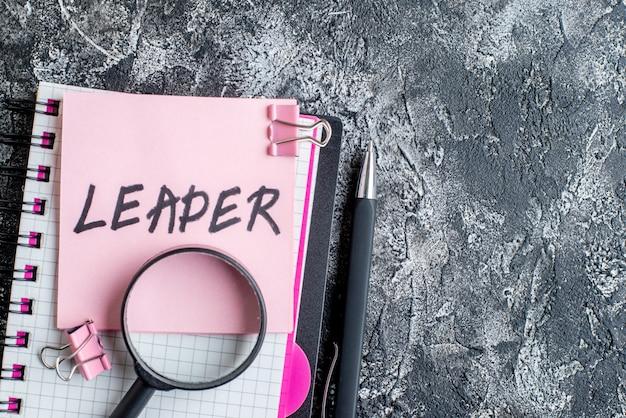 Widok z góry różowa naklejka z liderem napisanym długopisem i zeszytem na szarym tle