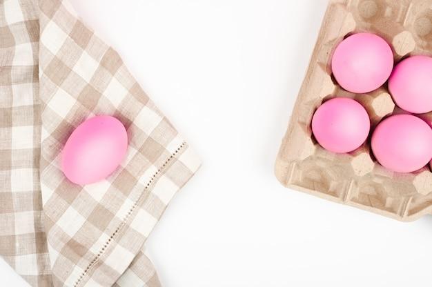 Widok z góry różowe jaja. miejsce na napis. biała kartka do pisania życzeń na wielkanoc. minimalistyczny trend, widok z góry. wielkanocna koncepcja.