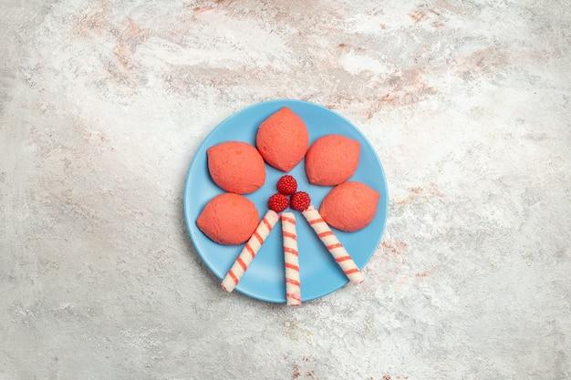 Widok z góry różowe pierniki wewnątrz płyty na białym tle ciasto biszkoptowe słodkie ciasteczka cukrowe