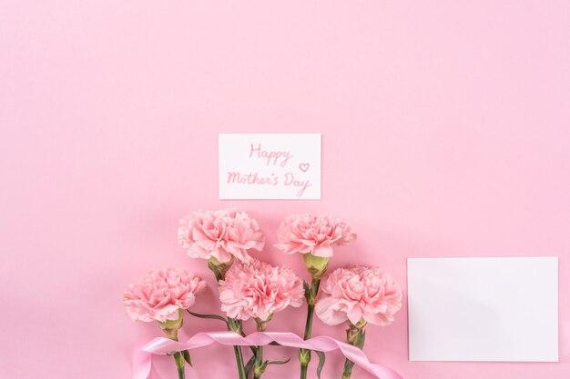 Widok z góry różowego goździka na różowym tle tabeli kwiat na dzień matki