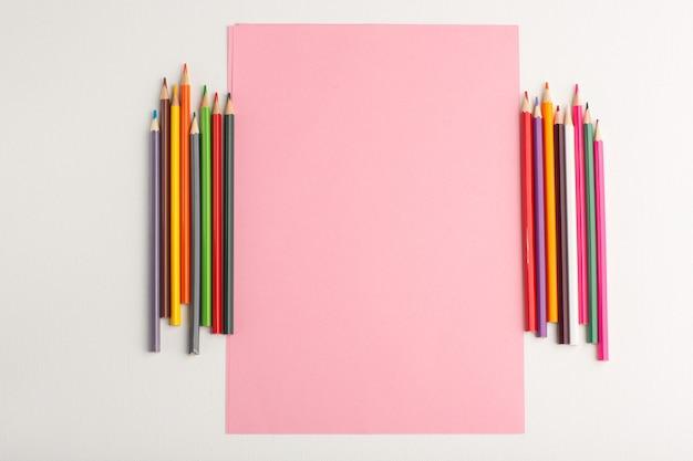 Widok z góry różowy papier puste z kolorowymi ołówkami na białej powierzchni