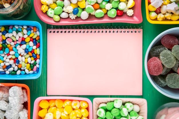 Widok z góry różowy szkicownik i miski z różnych kolorowych cukierków na zielonym tle