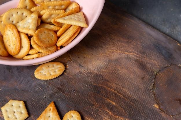 Widok z góry różowy talerz z krakersami i chipsami na szarym tle