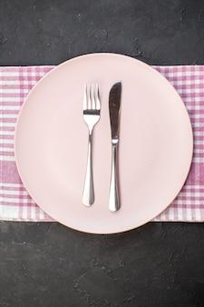 Widok z góry różowy talerz z widelcem i nożem na ciemnym tle