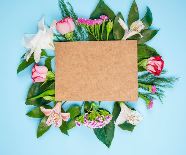 Widok z góry różowych róż i kwiatów alstremerii z goździkami tureckimi z brązową kartką papieru na niebieskim tle